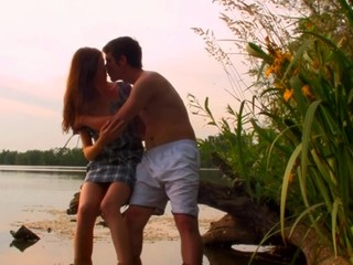 Sexy sex scene is taking place outdoors with a teen by the pond
